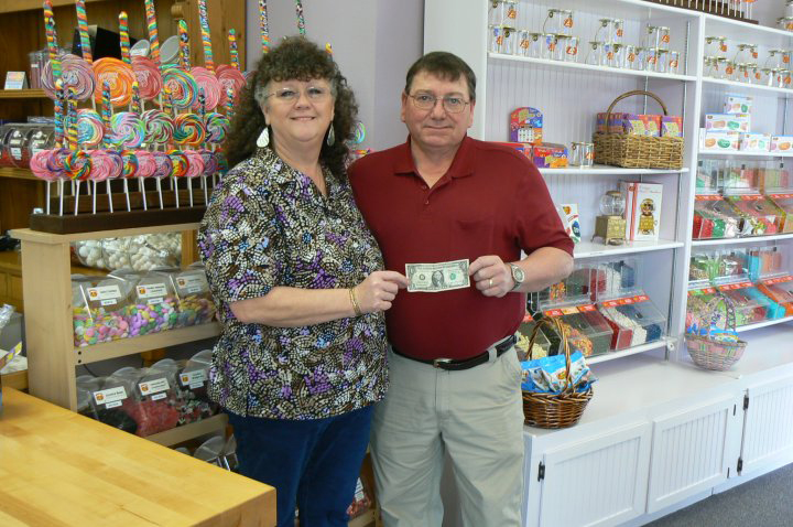 Whale's Tail owner Becky and husband Donnie showing the first dollar made at their shop.